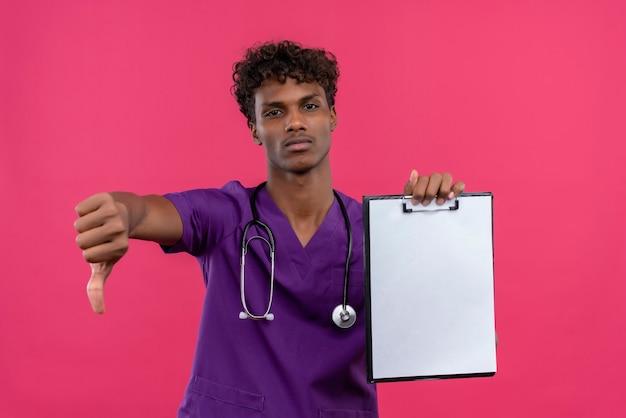 Młody przystojny ciemnoskóry lekarz z kręconymi włosami w fioletowym mundurze ze stetoskopem pokazujący schowek z pustą kartką papieru z kciukami w dół