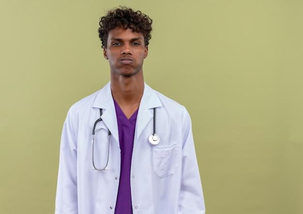 Młody przystojny ciemnoskóry mężczyzna z kręconymi włosami w białym fartuchu ze stetoskopem pyta o zmęczenie na zielonej przestrzeni