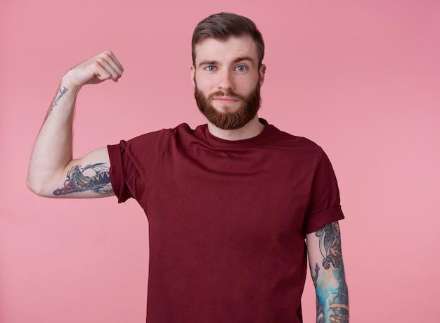 Młody przystojny czerwony brodaty mężczyzna w pustej koszulce, stoi na różowym tle, wygląda fajnie, dobrze się bawi i demonstruje siłę, patrzy w kamerę i uśmiecha się