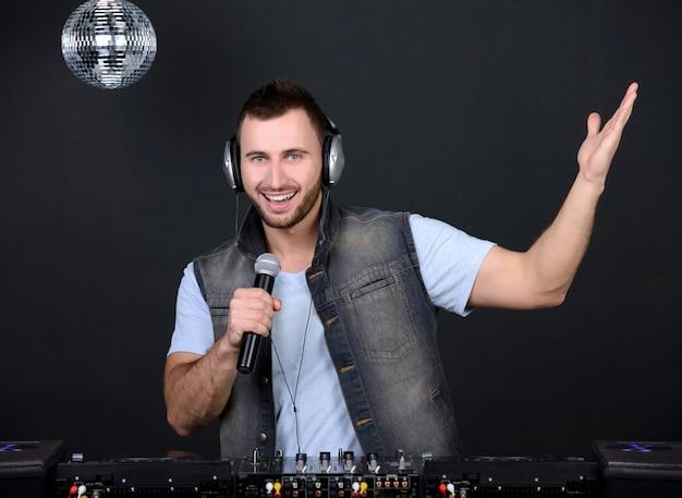 Młody przystojny deejay grający muzykę klubową.