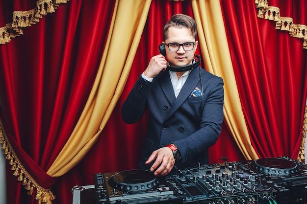 Młody przystojny dj gra muzykę w luksusowym, bogatym wnętrzu