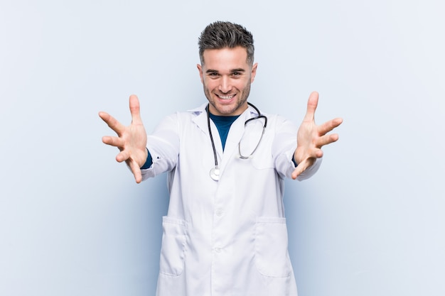 Młody przystojny doktor czuje się pewnie, przytulając się do.