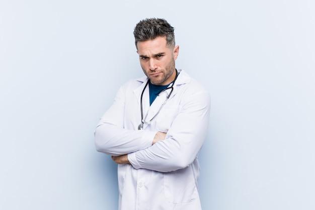 Młody przystojny doktor marszcząc brwi z niezadowoleniem, trzyma założone ręce.