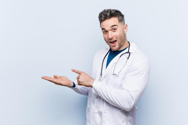 Młody przystojny doktor mężczyzna podekscytowany, trzymając kopię miejsca na dłoni.
