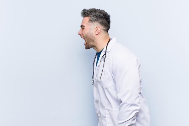 Młody przystojny doktorski mężczyzna krzyczy w kierunku odbitkowej przestrzeni