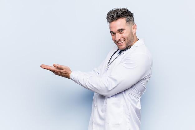 Młody przystojny doktorski mężczyzna trzyma dalej palmy.