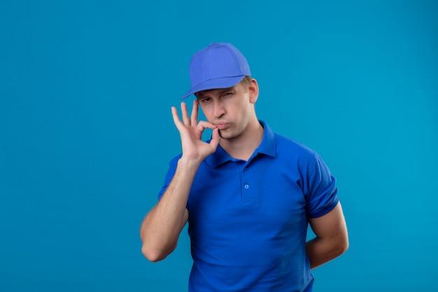 Młody przystojny doręczyciel w niebieskim mundurze i czapce robi gest ciszy, zamykając usta zamkiem błyskawicznym stojącym nad niebieską ścianą