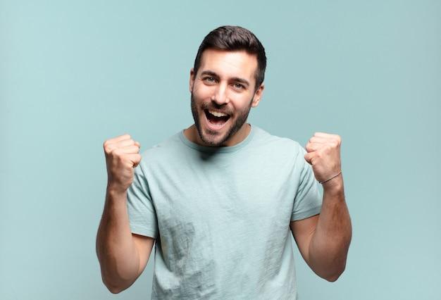 Młody przystojny dorosły mężczyzna czuje się szczęśliwy, pozytywny i odnosi sukcesy, świętuje zwycięstwo, osiągnięcia lub szczęście
