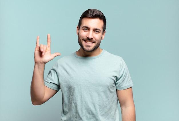 Młody przystojny dorosły mężczyzna czuje się szczęśliwy, zabawny, pewny siebie, pozytywny i zbuntowany, robi ręką rockowy lub heavy metalowy znak