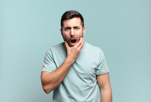 Młody, przystojny dorosły mężczyzna z szeroko otwartymi ustami i oczami oraz ręką na brodzie, czując się nieprzyjemnie zszokowany, mówiąc co lub wow
