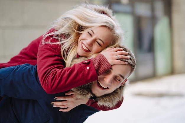 Młody przystojny facet daje girlfirend piggyback przejażdżkę