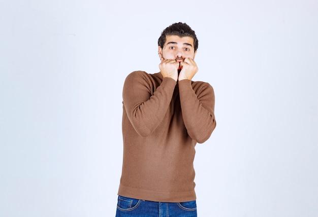 Młody przystojny facet model obejmujący usta pięściami.