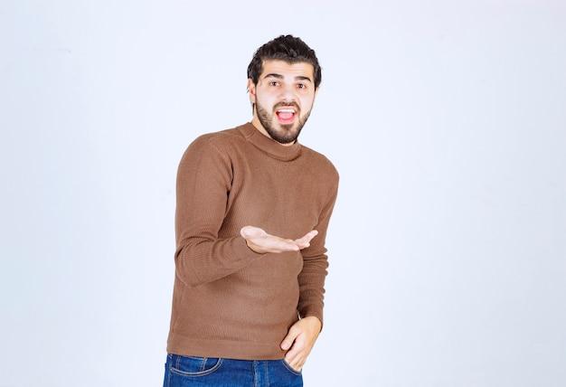 Młody przystojny facet model pokazano jego otwartej dłoni.