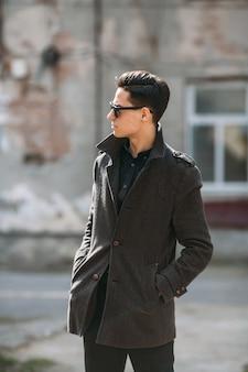 Młody przystojny facet pozuje na ulicy miasta