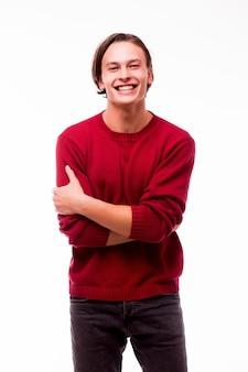 Młody przystojny facet pozuje niedbale na białym tle na białej ścianie