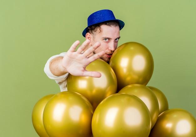 Młody przystojny facet słowiańskich imprezowiczów w kapeluszu imprezowym stojącym za balonami patrząc na kamerę wyciągającą rękę w kierunku kamery, wykonujący gest stopu na białym tle na oliwkowym tle