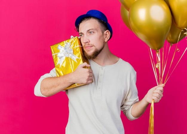 Młody przystojny facet słowiańskich imprezowiczów w kapeluszu, trzymając balony i dotykając twarzy z pudełkiem na prezent, patrząc na bok na białym tle na różowej ścianie