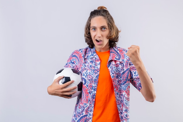 Młody przystojny facet trzymający piłkę nożną, wyglądający na podekscytowanego, cieszący się swoim sukcesem i zwycięstwem, zaciskający pięści z radością, szczęśliwy, że osiągnął swój cel i cele stojąc na białym tle