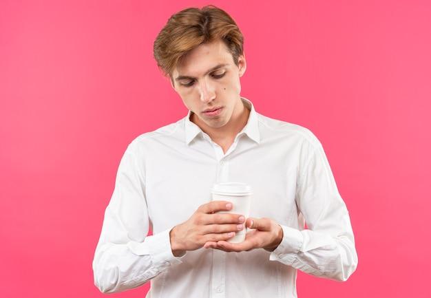 Młody przystojny facet ubrany w białą koszulę, trzymając i patrząc na filiżankę kawy