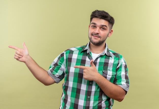 Młody przystojny facet ubrany w kraciastą koszulę uśmiechnięty, wskazujący w prawo z palcami wskazującymi stojącymi nad ścianą khaki