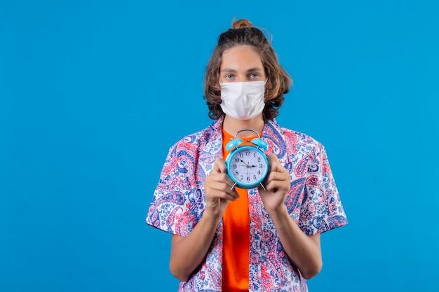 Młody przystojny facet ubrany w maskę ochronną na twarz, trzymając budzik, patrząc na kamery z poważnym wyrazem pewności, stojąc na niebieskim tle