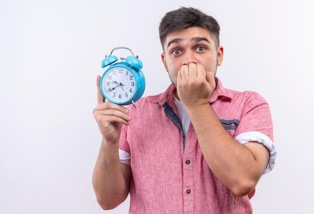Młody przystojny facet ubrany w różową koszulkę polo boi się spóźnienia trzymając budzik stojący nad białą ścianą