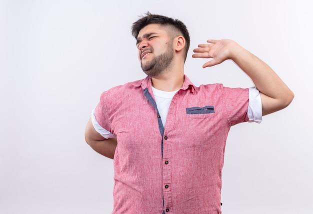 Młody przystojny facet ubrany w różową koszulkę polo, cierpiący na bóle pleców, stojący na białej ścianie