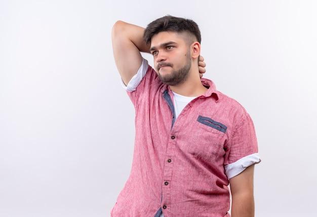 Młody przystojny facet ubrany w różową koszulkę polo, patrząc w zamyśleniu oprócz drapania się po głowie stojącej na białej ścianie