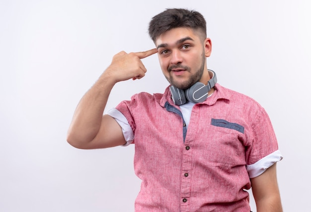Młody przystojny facet ubrany w różową koszulkę polo, wskazując na swój mózg, prosząc o myślenie stojąc nad białą ścianą
