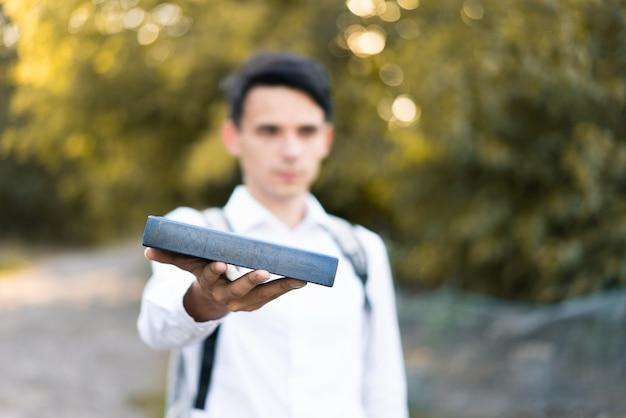 Młody przystojny facet w białej koszuli trzyma książkę w ręku i wyciąga ją. selektywna ostrość. na świeżym powietrzu.