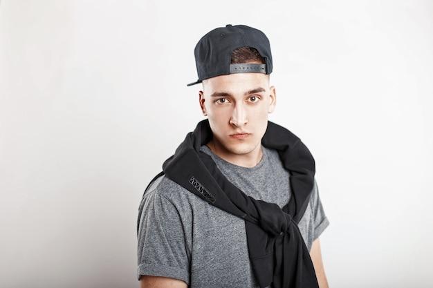 Młody przystojny facet w czapce z daszkiem, szarej koszuli na białym tle