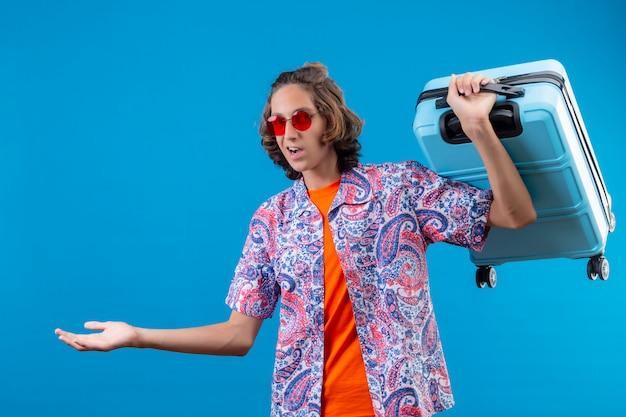 Młody przystojny facet w czerwonych okularach przeciwsłonecznych, trzymając walizkę podróżną nieświadomy i zdezorientowany, nie mając odpowiedzi, rozkładając ramiona na stojąco