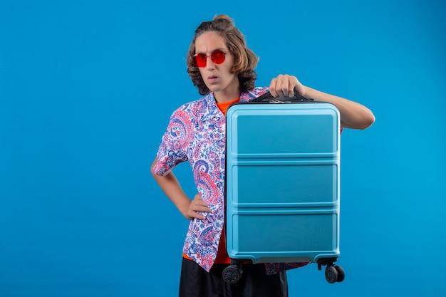 Młody przystojny facet w czerwonych okularach przeciwsłonecznych, trzymając walizkę podróżną, patrząc na kamery zaskoczony i zdezorientowany stojąc na niebieskim tle