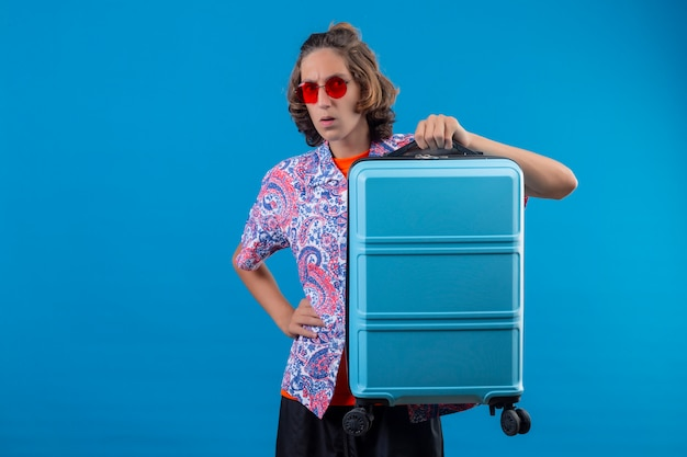 Młody przystojny facet w czerwonych okularach przeciwsłonecznych, trzymając walizkę podróżną, patrząc na kamery, zaskoczony i zdezorientowany stojąc