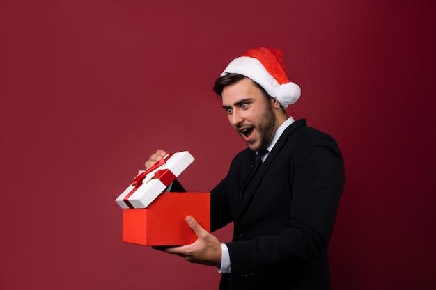 Młody przystojny facet w garniturze i santa hat z pudełko