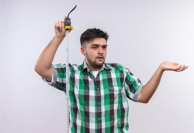 Młody przystojny facet w kraciastej koszuli niezdecydowany trzymający mierniczy patrząc poza tym, nie wie, co robić stojąc nad białą ścianą
