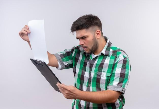 Młody przystojny facet w kraciastej koszuli patrząc na schowek wstrząśnięty, stojąc nad białą ścianą