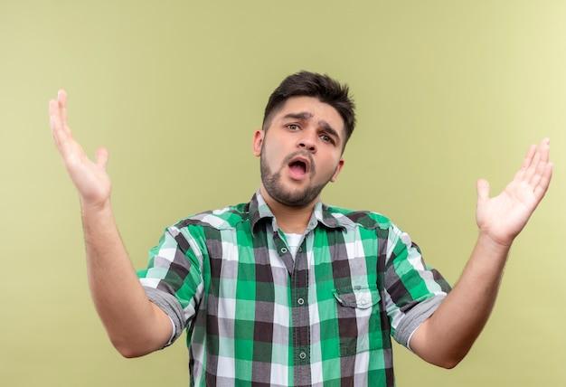 Młody przystojny facet w kraciastej koszuli wyglądający na zdezorientowanego nie wie, co robić, stojąc nad ścianą koloru khaki