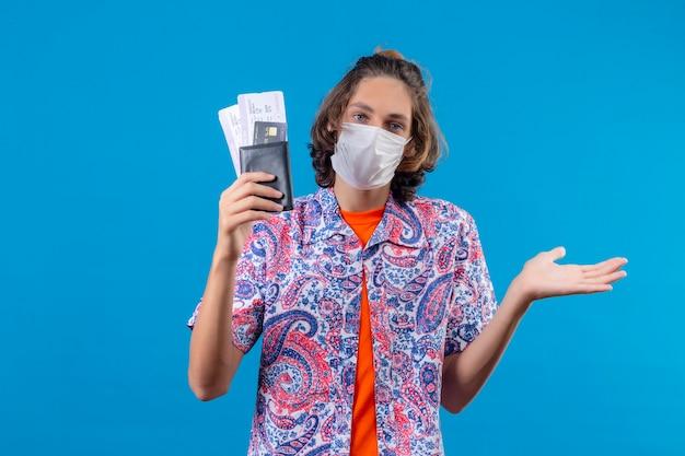 Młody przystojny facet w masce ochronnej na twarz, trzymając bilety lotnicze nieświadomy i zdezorientowany, nie mając odpowiedzi, rozkładając ręce stojące na niebieskim tle