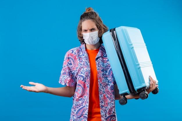 Młody przystojny facet w masce ochronnej na twarz, trzymając walizkę podróżną, patrząc na kamerę z marszczoną twarzą, robiąc gest ręką, zadając pytanie stojąc na niebieskim tle