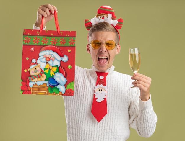 Młody przystojny facet w opasce świętego mikołaja i krawacie, patrząc na kamerę, trzymając kieliszek szampana i podnosząc torbę z prezentami świątecznymi i krzycząc z zamkniętymi oczami na tle oliwkowej zieleni