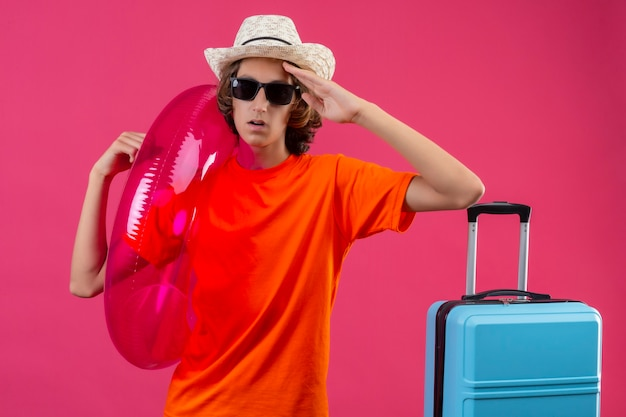 Młody przystojny facet w pomarańczowej koszulce i letnim kapeluszu w czarnych okularach przeciwsłonecznych, trzymając nadmuchiwany pierścień dotykający głowy za pomyłkę, wyglądający na zdezorientowanego stojącego z walizką podróżną nad różowym backgrou