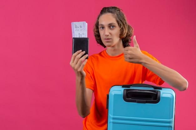 Młody przystojny facet w pomarańczowej koszulce stojącej z walizką podróżną, trzymając bilety lotnicze, patrząc na kamerę pozytywnie i szczęśliwie pokazując kciuki do góry na różowym tle