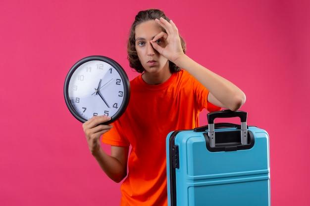 Młody przystojny facet w pomarańczowej koszulce stojącej z walizką podróżną, trzymając zegar robi ok znak patrząc przez ten znak na różowym tle