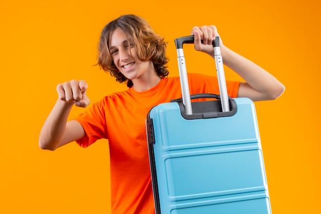 Młody przystojny facet w pomarańczowej koszulce trzyma walizkę podróżną, wskazując palcem na aparat, uśmiechając się wesoło wyglądając szczęśliwie i pozytywnie stojąc na żółtym tle