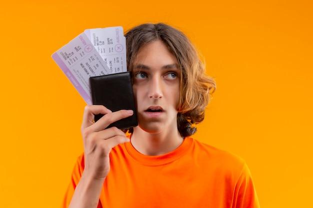 Młody przystojny facet w pomarańczowej koszulce trzymając bilety lotnicze patrząc na bok zdezorientowany ze smutnym wyrazem twarzy