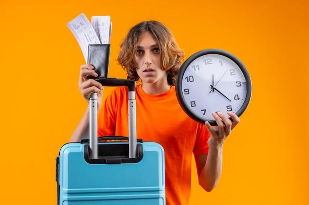 Młody przystojny facet w pomarańczowej koszulce, trzymając walizkę podróżną i bilety lotnicze, stojący z zegarem, patrząc zdezorientowany na żółtym tle