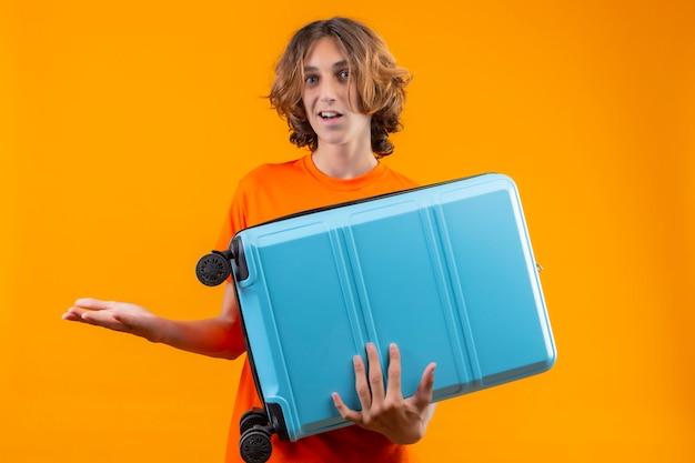 Młody przystojny facet w pomarańczowej koszulce, trzymając walizkę podróżną nieświadomy i zdezorientowany, nie mając odpowiedzi, rozkładając ręce na stojąco