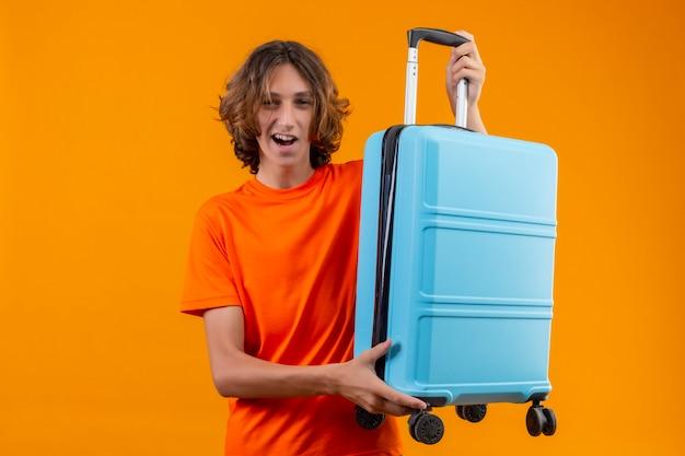 Młody przystojny facet w pomarańczowej koszulce, trzymając walizkę podróżną, uśmiechając się wesoło pozytywnie i szczęśliwie gotowy do podróży stojąc na żółtym tle