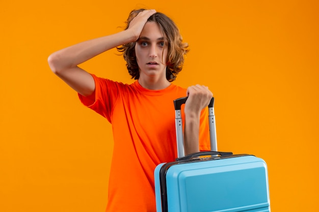 Młody przystojny facet w pomarańczowej koszulce trzymającej walizkę podróżną stojąc z ręką na głowie za błąd wyglądający na zdezorientowanego pamiętaj o błędzie na żółtym tle